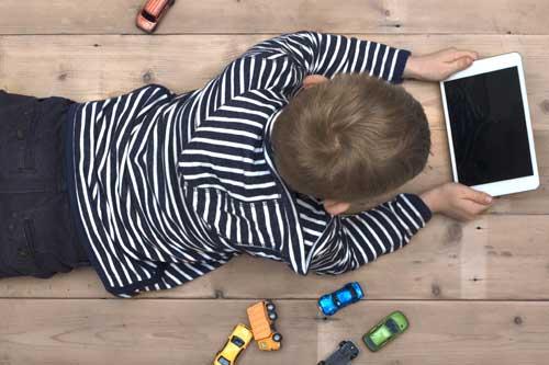 Kind sitzt vor einem Tablet